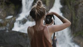 年轻无固定职业的摄影师女孩在密林拍摄在石头的一个美好的大瀑布身分 股票视频