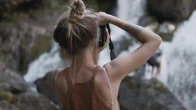 年轻无固定职业的摄影师女孩在密林拍摄在石头的瀑布身分 影视素材