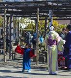 年轻日本妇女在黄色和服穿戴了,有在蓝色和服的小男孩跳舞的,浅草,日本, 2018年 图库摄影