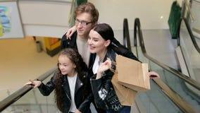 年轻时兴的家庭在一个购物中心的乘坐一个自动扶梯与袋子 股票录像