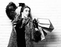 年轻时兴的性感的俏丽的富有的愉快的妇女或女孩有美丽的长的金发的在灰色毛皮腰部外套与 免版税库存照片