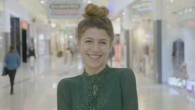 年轻时尚女性博客作者笑的摆在和看在购物中心的照相机画象在她的购物会议前- 股票录像