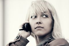 年轻时尚白肤金发的女商人谈话在室外的手机 图库摄影