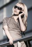 年轻时装业妇女谈话在手机在办公楼 免版税库存照片