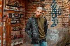 年轻时髦的人以军事时尚在墙壁附近穿衣与 库存照片