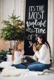 年轻时髦的俏丽的妇女祝贺礼服的女儿在家使用用手的xmas 小女孩感谢她 图库摄影
