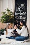年轻时髦的俏丽的妇女祝贺礼服的女儿在家使用用手的xmas 小女孩感谢她 库存图片
