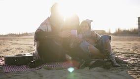 年轻时髦的家庭画象在casualwear的坐格子花呢披肩由海滨和有热的饮料在野餐 ? 股票视频