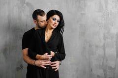 年轻时髦的美好的华美的夫妇,反对在家灰色墙壁顶楼在演播室或 库存图片