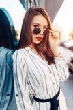 年轻时髦的行家妇女走在街道上的,佩带的逗人喜爱的时髦成套装备夏天晴朗的生活方式时尚画象  免版税库存照片