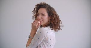 年轻时髦的长发卷曲微笑白种人女性扔的头发特写镜头射击愉快地看照相机与 影视素材
