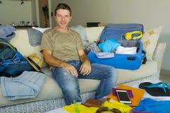 年轻有吸引力和愉快的人在家客厅长沙发包装手提箱和背包组织的护照和准备好旅行的事 库存图片