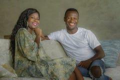 年轻有吸引力和愉快的黑美国黑人的夫妇在家放松了微笑沙发长沙发谈的甜点一起享用和  免版税库存照片