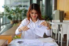 年轻有吸引力的亚洲女商人撕毁的文书工作或图在她的办公室背景中 免版税库存图片