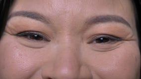 年轻有吸引力的亚洲女性面孔特写镜头射击与看直接与微笑的表情的照相机的眼睛的 股票录像