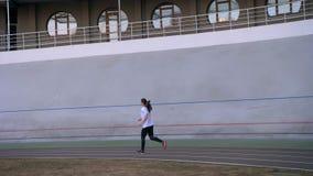 年轻有吸引力的体育场的适合白种人女性跑步的户外特写镜头画象在都市城市 股票视频