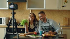 年轻有吸引力的关于烹调的夫妇射击录影食物博克在dslr照相机在厨房里 库存图片