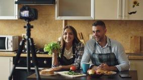年轻有吸引力的关于烹调的夫妇射击录影食物博克在dslr照相机在厨房里 免版税库存照片