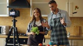 年轻有吸引力的关于烹调的夫妇射击录影食物博克在dslr照相机在厨房里 库存照片