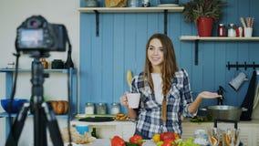 年轻有吸引力的关于烹调的妇女录音录影食物博克在dslr照相机在厨房里 图库摄影