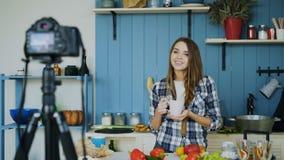年轻有吸引力的关于烹调的妇女录音录影食物博克在dslr照相机在厨房里 免版税库存照片