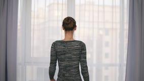 年轻有吸引力的妇女开幕后面看法在一个大窗口和让光的在屋子里 看  股票视频