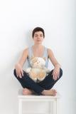 年轻有吸引力的微笑的女子实践的瑜伽,坐在半莲花锻炼Ardha Padmasana姿势,制定出佩带 图库摄影