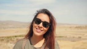 年轻有吸引力的微笑的被混合的赛跑的女孩画象在沙漠 摆在与挥动在风的头发的照相机的愉快的旅游妇女 股票录像