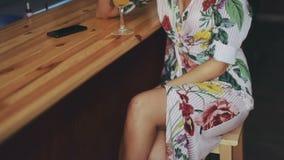 年轻有吸引力的性感的妇女白色礼服酒吧微笑鸡尾酒秸杆饮料橙色全视图时兴画象移动 影视素材