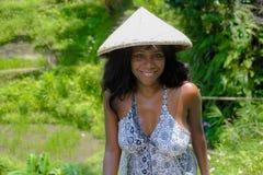 年轻有吸引力的愉快的美国黑人的黑人妇女30s探索的米在佩带农村传统Asi的巴厘岛调遣森林和密林 免版税库存图片