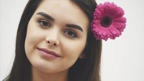 年轻有吸引力的有桃红色花的温泉式样妇女,隔绝在白色背景 面孔美女模型与 影视素材