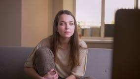 年轻有吸引力的白种人女性看着电视特写镜头画象有兴奋的坐长沙发户内在 影视素材