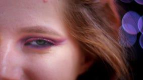 年轻有吸引力的白种人女性面孔特写镜头射击与半应用的看照相机与的闪烁桃红色构成的 股票录像