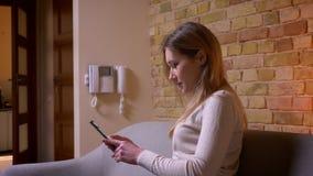 年轻有吸引力的白种人深色的女性浏览网络特写镜头画象在选址在长沙发的电话的户内 股票视频
