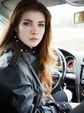 年轻有吸引力的红色回顾从驾驶席的头发自己经营的女商人司机接近的画象困住在a 免版税图库摄影