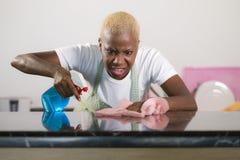 年轻有吸引力的被注重的和生气美国黑人的妇女洗涤的kitch洗涤剂浪花瓶和布料清洁回家厨房 库存图片