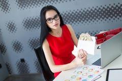 年轻有吸引力businesslady在红色礼服和玻璃坐在Th 免版税图库摄影