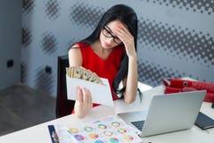 年轻有吸引力businesslady在红色礼服和玻璃坐在Th 免版税库存照片