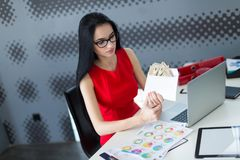 年轻有吸引力businesslady在红色礼服和玻璃坐在Th 免版税库存图片