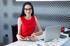 年轻有吸引力businesslady在红色礼服和玻璃坐在Th 库存图片