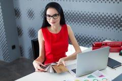 年轻有吸引力businesslady在红色礼服和玻璃坐在Th 图库摄影