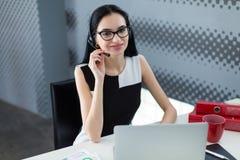 年轻有吸引力businesslady在黑礼服和玻璃坐在 库存图片