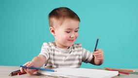 年轻有天才的男孩画在册页的一副铅笔图在蓝色背景 影视素材