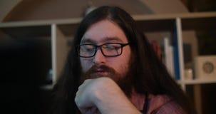 年轻有胡子的与膝上型计算机的人佩带的玻璃工作在黑暗的办公室后在晚上,他的面孔由屏幕打开了 股票录像