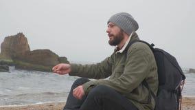 年轻有胡子的人单独坐海滩在晚上并且投掷小卵石入水 影视素材