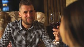 年轻有胡子的人在与一杯的一个日期酒在他的手上谈话与他的女朋友 股票视频