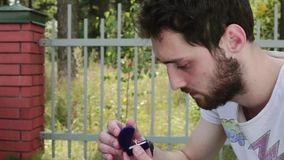 年轻有胡子的人在篱芭旁边打开有婚戒的小蓝色天鹅绒箱子 股票录像