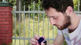 年轻有胡子的人在篱芭旁边打开空的蓝色天鹅绒婚戒小盒子 股票视频