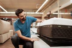 年轻有胡子的人测试在家具店的床垫 一个健康姿势的矫形床垫 免版税库存照片