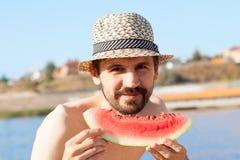 年轻有胡子的人用在海滩的一个西瓜 免版税库存照片